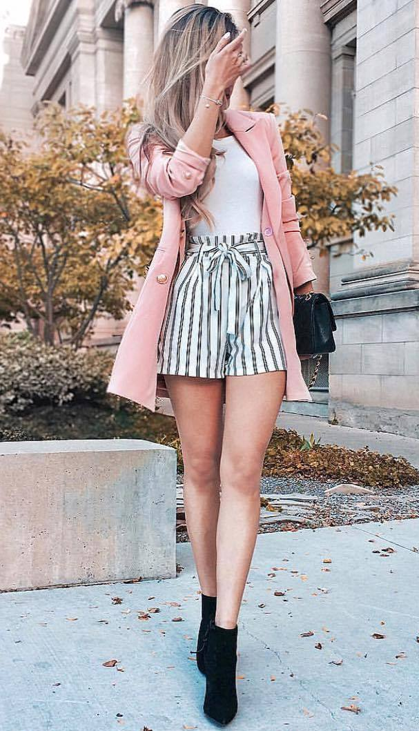 how to wear a pair of striped shorts : black boots + black bag + white top + pink coat