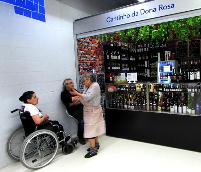 Senhora numa cadeira de rodas, senhor sentado e outra senhora a falar em frente à uma banca de vinhos no Mercado Temporário do Bolhão