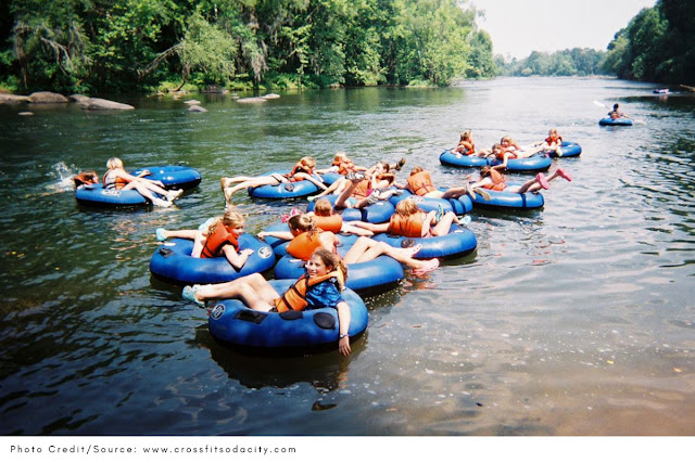 youth group in inner tubes floating down a river