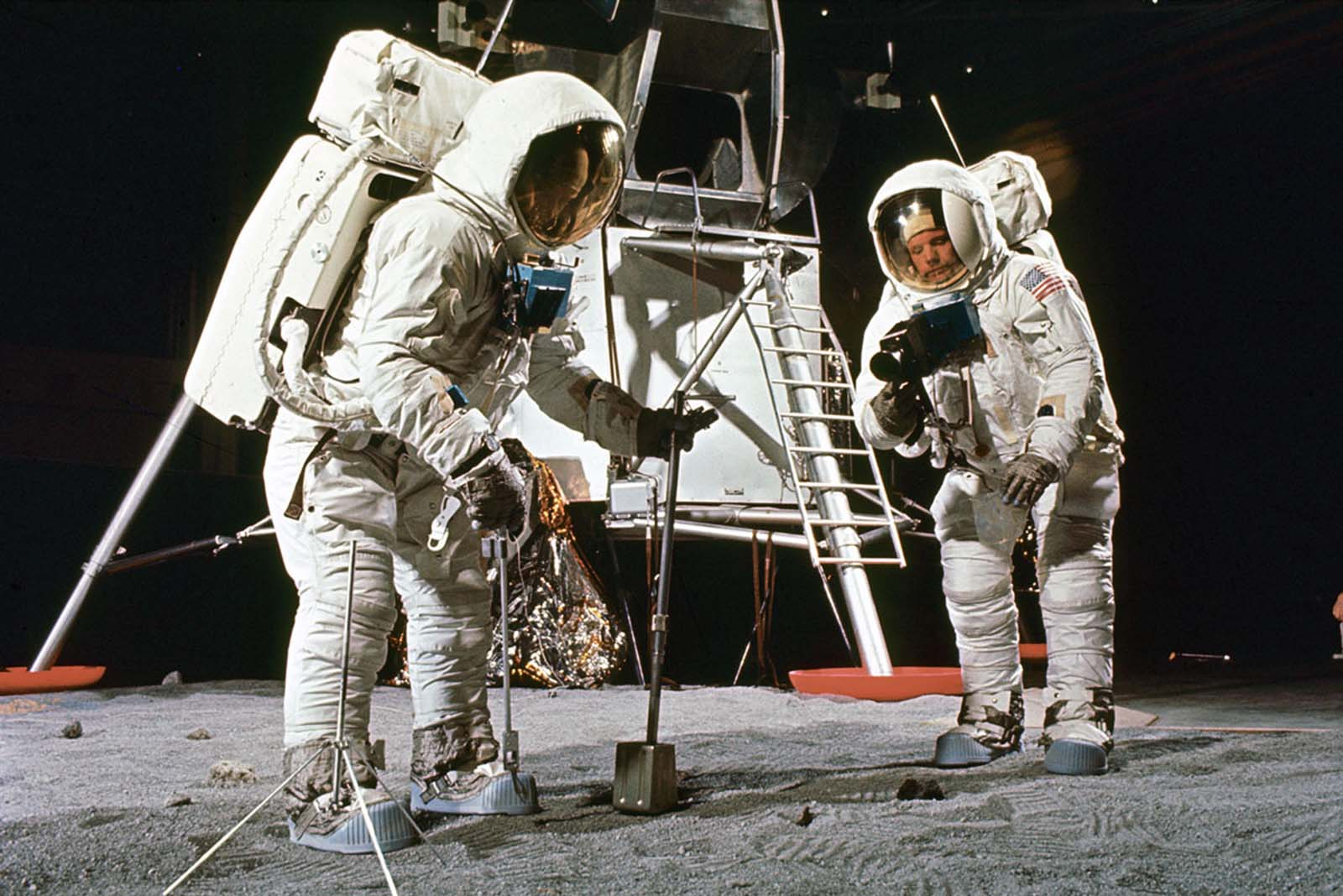 Buzz Aldrin (left) and Neil Armstrong train to make documented sample retrievals, suited up near a mock-up of the lunar lander in the spring of 1969.