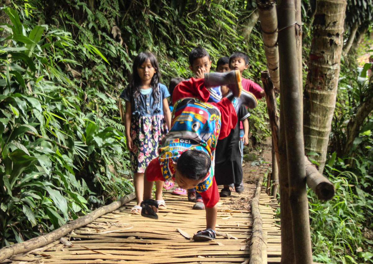 With his mum in tow, the gap-toothed pupil crawls from his West Java village across rocky paths and an old wooden bridge that he navigates on his hands alone, as his sneakers dangle in the air.