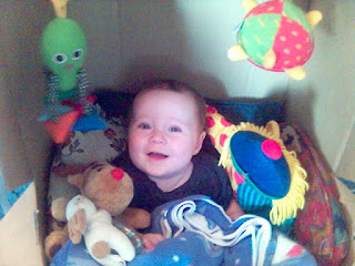 Baby Happily sitting in Cardboard Box with Toys
