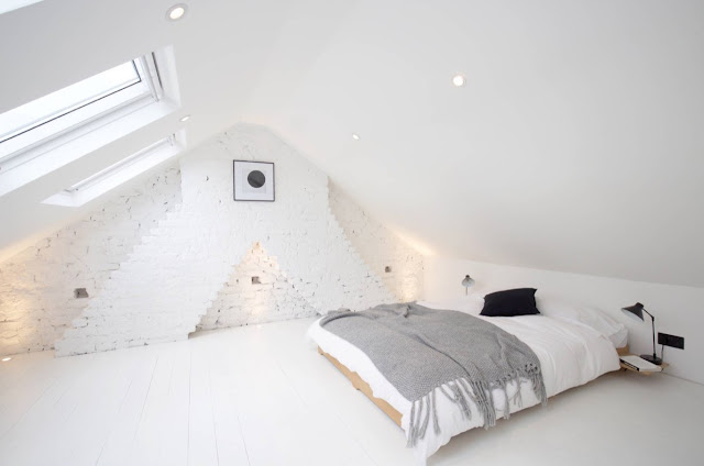 Set in an attic space, a low-lying bed draws the eye with a grey throw and black bedside lamp