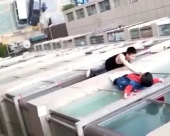 WATCH Heart-stopping moment Boy, 5, climbs out of window and clings to ledge of his 13th-floor home after parents left him alone at home