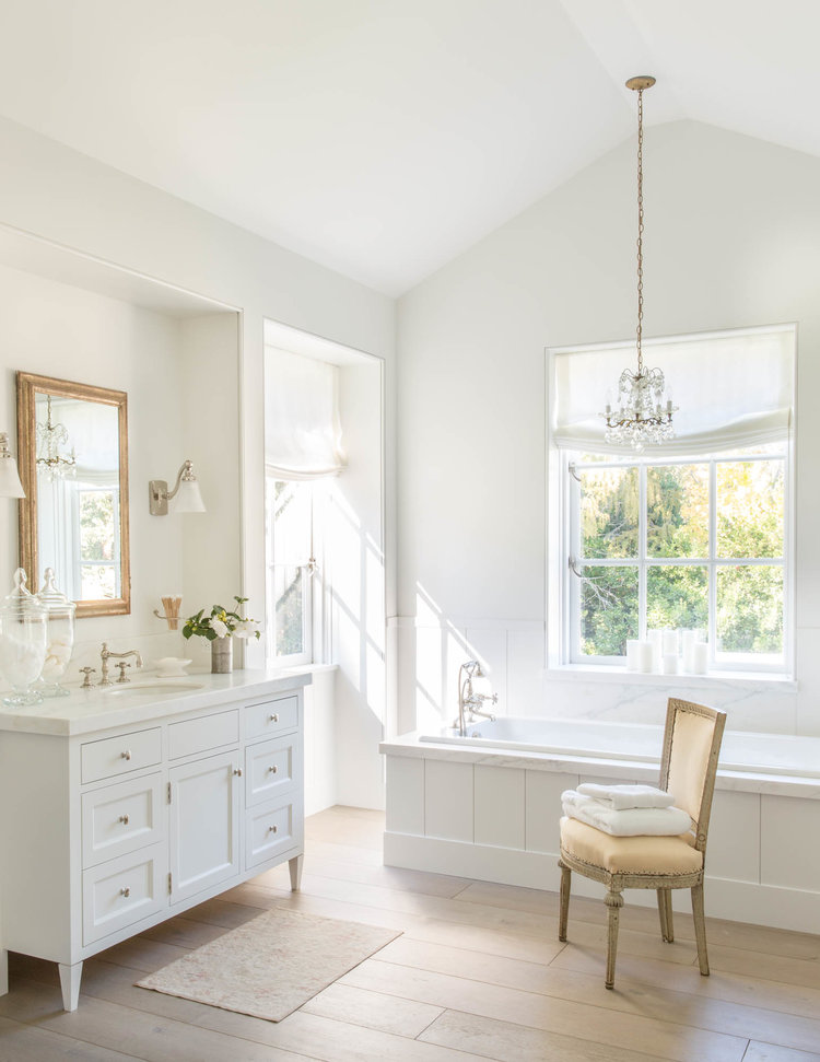 Stunning white bathroom with wood floors in a California modern farmhouse by Giannetti Home