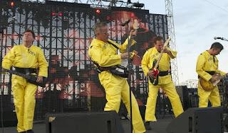 Devo en vivo en el Forecastle Festival, Louisville, Kentucky, 2010 De izquierda a derecha: Gerald Casale (bajo), Mark Mothersbaugh (voces; teclados), Bob Casale (teclados; sintes; guitarra),y Bob Mothersbaugh (guitarra)