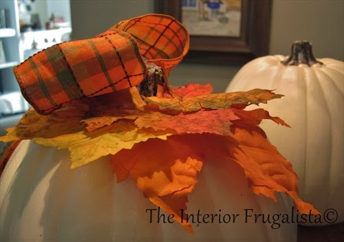 Layer and attach fabric leaves and the bow to the top of the pumpkin with a hot glue gun.