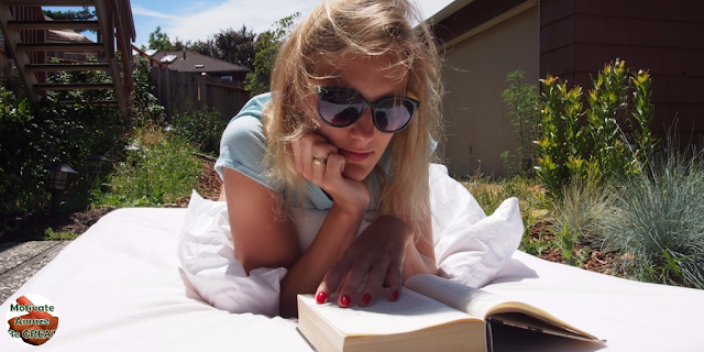 "Featured in the article: ""25 Quotes About Reading That Will Get You Opening Books"". Girl reading a book, motivated. Sunglasses."
