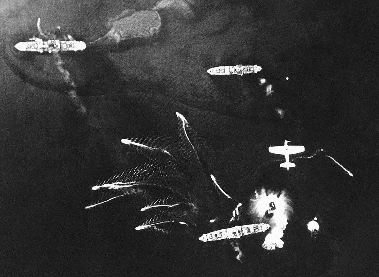 Small Japanese craft flee from larger vessels during an American aerial attack on Tonolei Harbor, Japanese base on Bougainville Island, in the Central Solomon Islands on October 9, 1943.