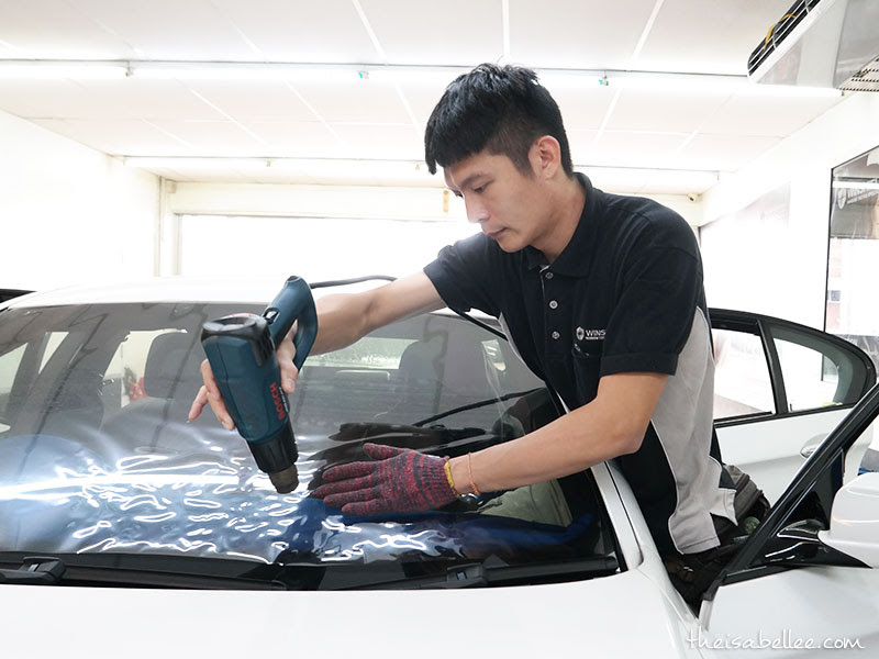 Applying window tinting at Winshield