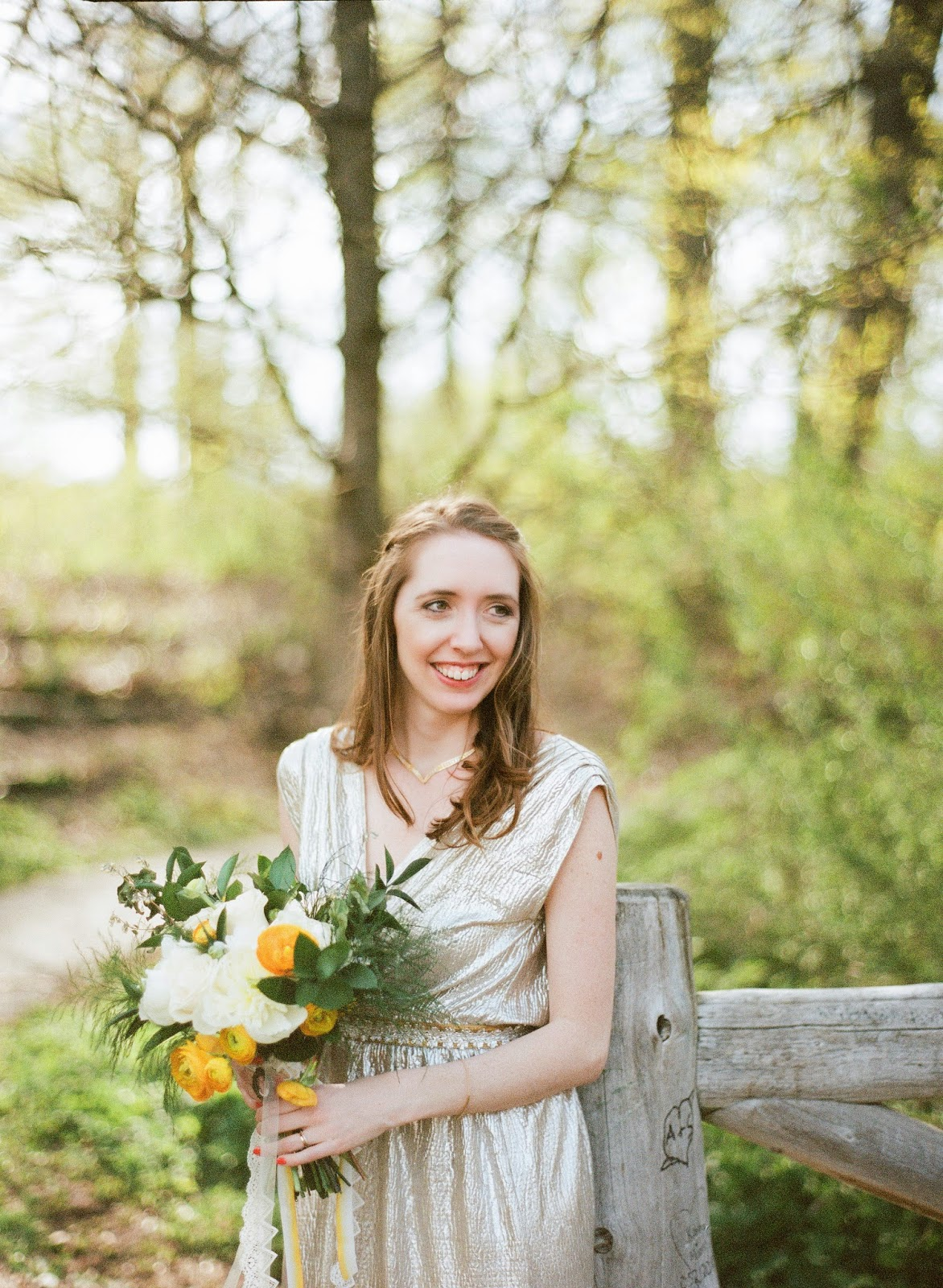brooklyn, new york bride in a gold dress holding a yellow ranunculus and white peony spring bouquet at her prospect park wedding