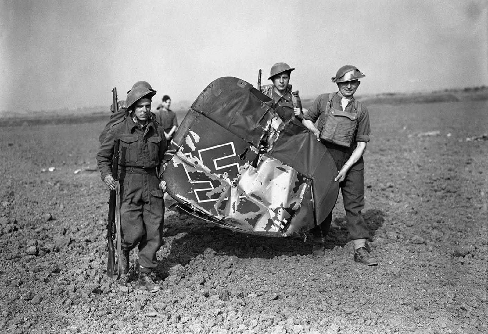 Soldiers carrying off the tail of a Messerschmitt 110, which was shot down by fighter planes in Essex, England, on September 3, 1940.