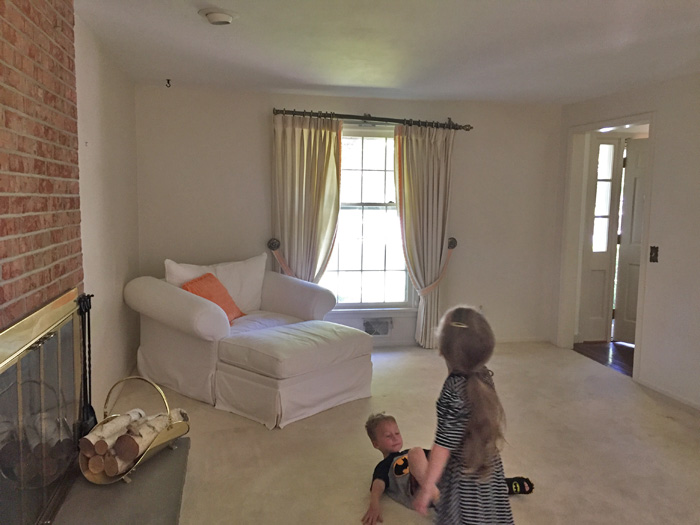 Living room with white carpet and brick fireplace and kids playing on the floor