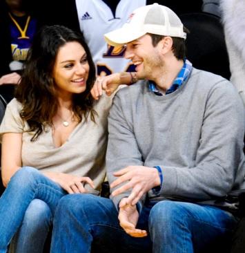 Foto de Ashton Kutcher sentado feliz con Mila Kunis