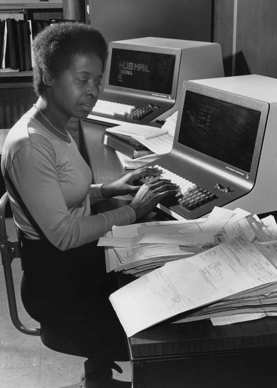 An office worker logs addresses into a Data General computer at a direct-mail company in Boston, Massachusetts. She wears a knit, fitted top; her hair is naturally styled and worn short. 1980.