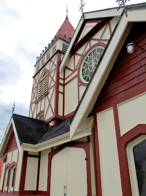 Front of a mock-tudor style wooden church.