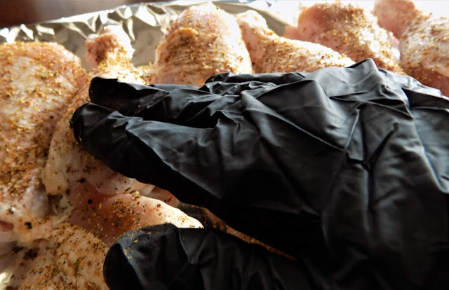 This is a picture of chicken legs being rubbed with seasoning