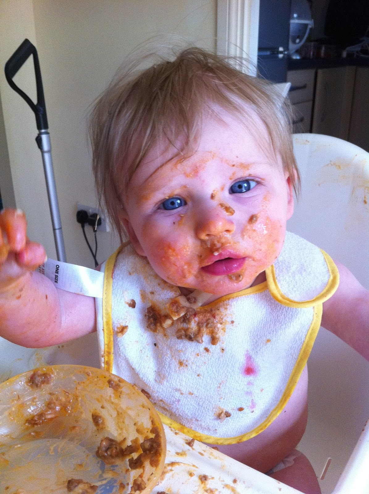 A baby covered in bolognase sauce reaches out a messy hand