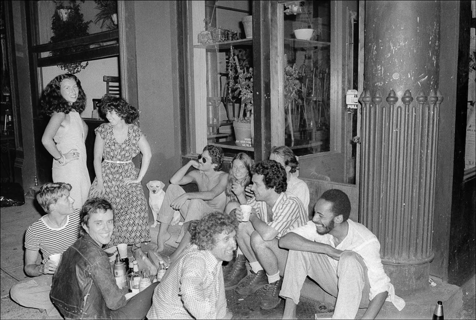 A group of people hold a party on a SoHo sidewalk.
