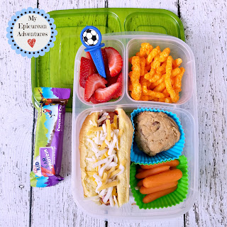 Lunch box fun with a hot dog sprinkled with cheese on top. In our @easylunchboxes #lunchboxideas