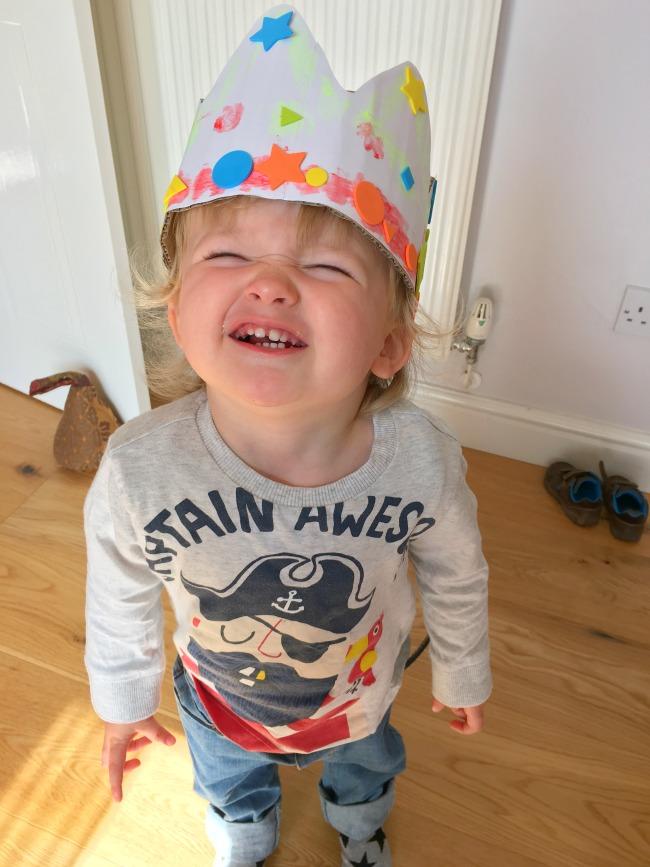 toddler wearing his crown with big smile