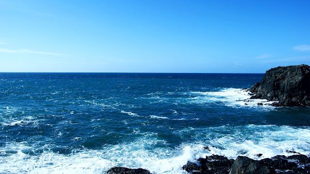 De zee en een strak blauwe lucht met rotsen