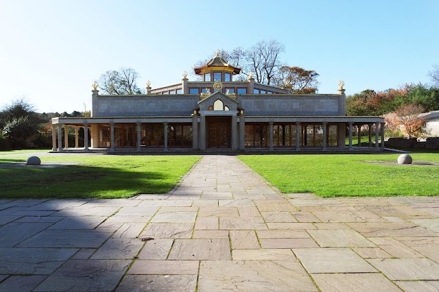 conishead priory buddhist temple: a large grey building sat in a garden. It has pillars, floor-to-ceiling windows, and golden statues on the roof