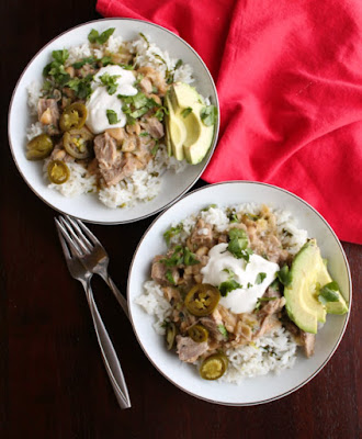 salsa verde pork burrito bowls with sour cream, jalapenos, cilantro and slices of avocado