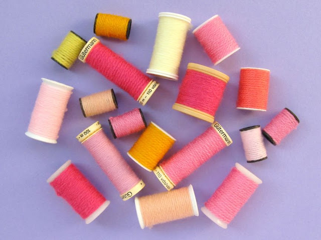 old sewing thread reels wrapped with colourful yarn