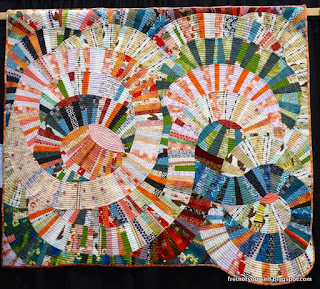 Improvisational quilt of large curves of pink, coral, cream strips with smaller touches of green, blue and red circle and loop across the surface.