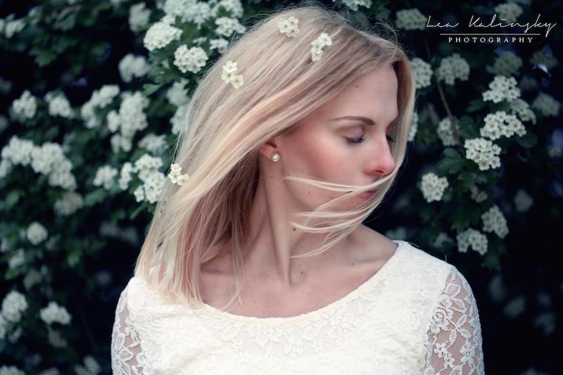 blonde Frau mit wehenden Haaren und Blüten