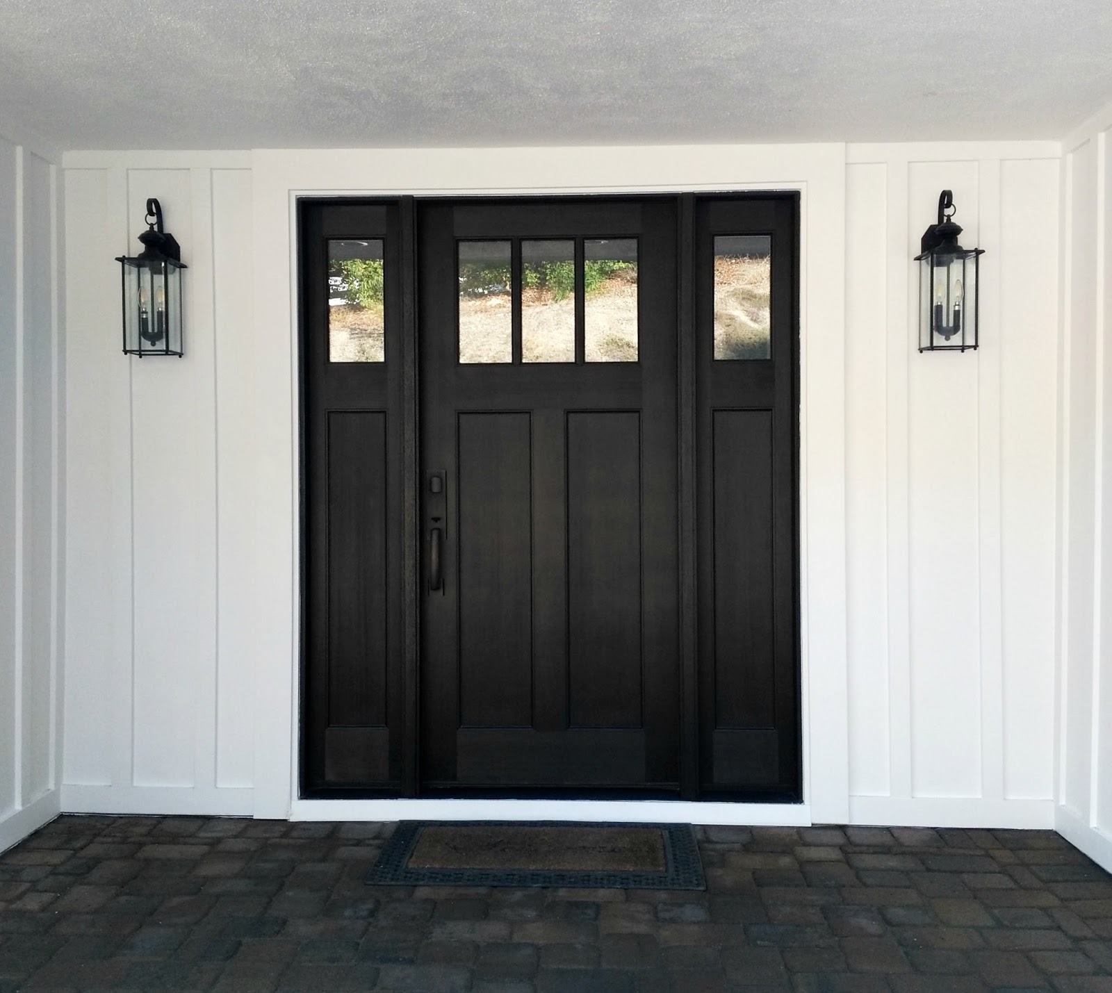 craftsman style black front door exterior home improvements entryway porch board and batten black and white
