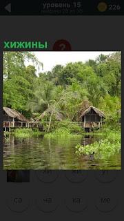 На берегу озера расположены несколько хижин с мостиками между ними