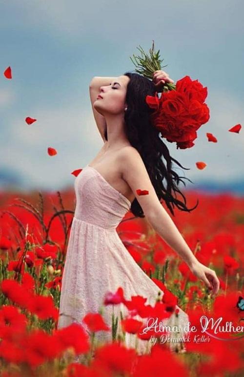 Uma jovem num campo florido, sente o aroma das flores.