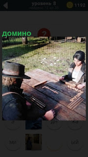 На улице за столом женщина играет в домино с мужчиной