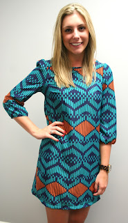 A Tribal Beauty dress in blue, rusty red, and turquoise by A Cut Above, as seen from the front, worn by a blond model.