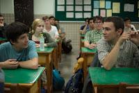 Nathan y su compañero con que es muy directo sentados en bancos escolares