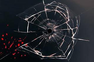 vidro trincado e perfurado por arma de fogo e salpicos de sangue