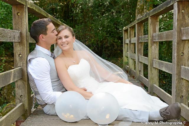 photo mariés assis sur pont de bois bisous à la mariée
