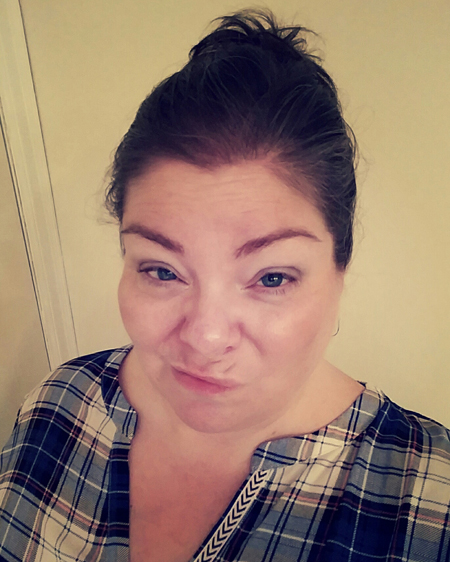 image of me, a fat white woman, making a stinkface, wearing a plaid shirt with my hair pulled up