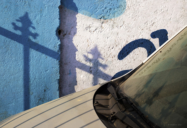 A Minimalist Photo of a part of an Abandoned Car, parked against a textured Indian Wall in Jaipur City.