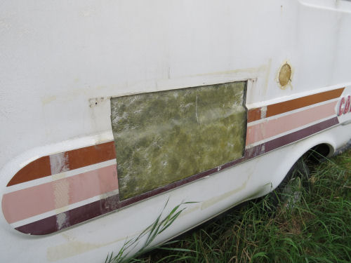 side of a fiberglass trailer with big repaired area