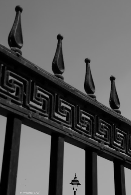 A Black and White Minimal Art Photograph of a Distant Lamp as seen through the metal fence at Masala Chowk, Jaipur, India. Shot Captured with Canon 6D Mark II Camera.