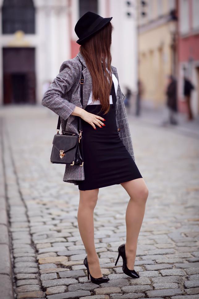 Tweedowy płaszcz, koszula z kokardą, ołówkowa spódniczka, kapelusz i rajstopy ze szwem