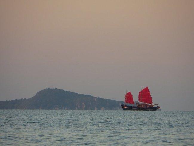 Старый корабль с красными парусами во время заката