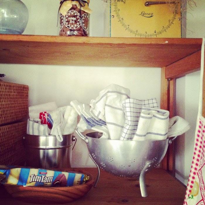 アンティークのコランダーにおしゃれにふきんを入れたキッチンの棚
