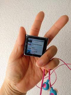 ピースサインの掌の中にiPodminiとイヤフォン