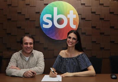 Chris Flores assina contrato ao lado do Diretor de Planejamento Artístico e de Criação Fernando Pelegio. Crédito da imagem: Cauana Fernandes/SBT