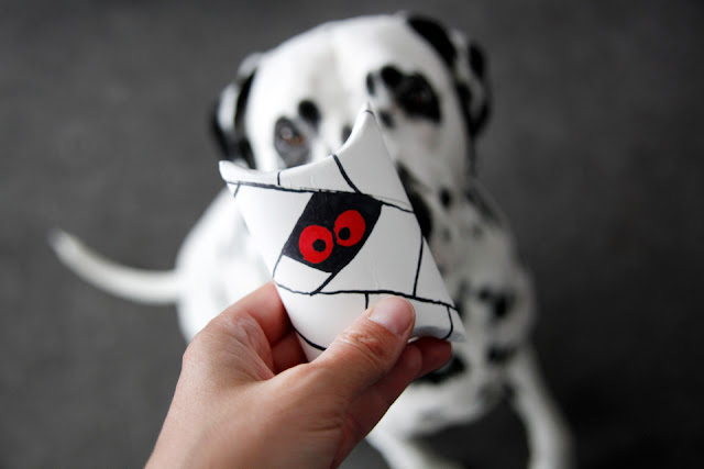 Dalmatian dog begging for treats from a Halloween mummy treat box
