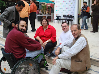 Simon sitting on some conrete steps, with an Egyptian man wheelchair user and two other people